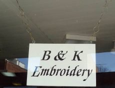 B & K Embroidery sign hanging in a window