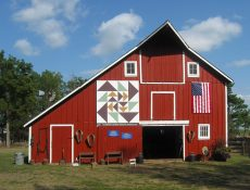 Red barn with a barn quilt and American flag
