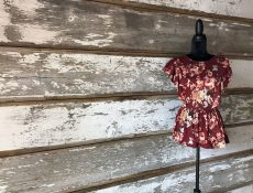 Maroon floral top displayed on a mannequin