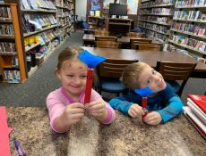 Young boy & girl hold up Dr. Seuss crafts