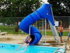 Kids taking turns on the swimming pool slide