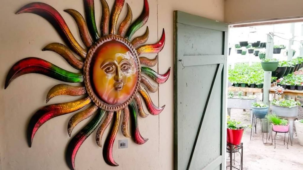 Large sun decoration hangs on a wall next to an open door leading into greenhouse