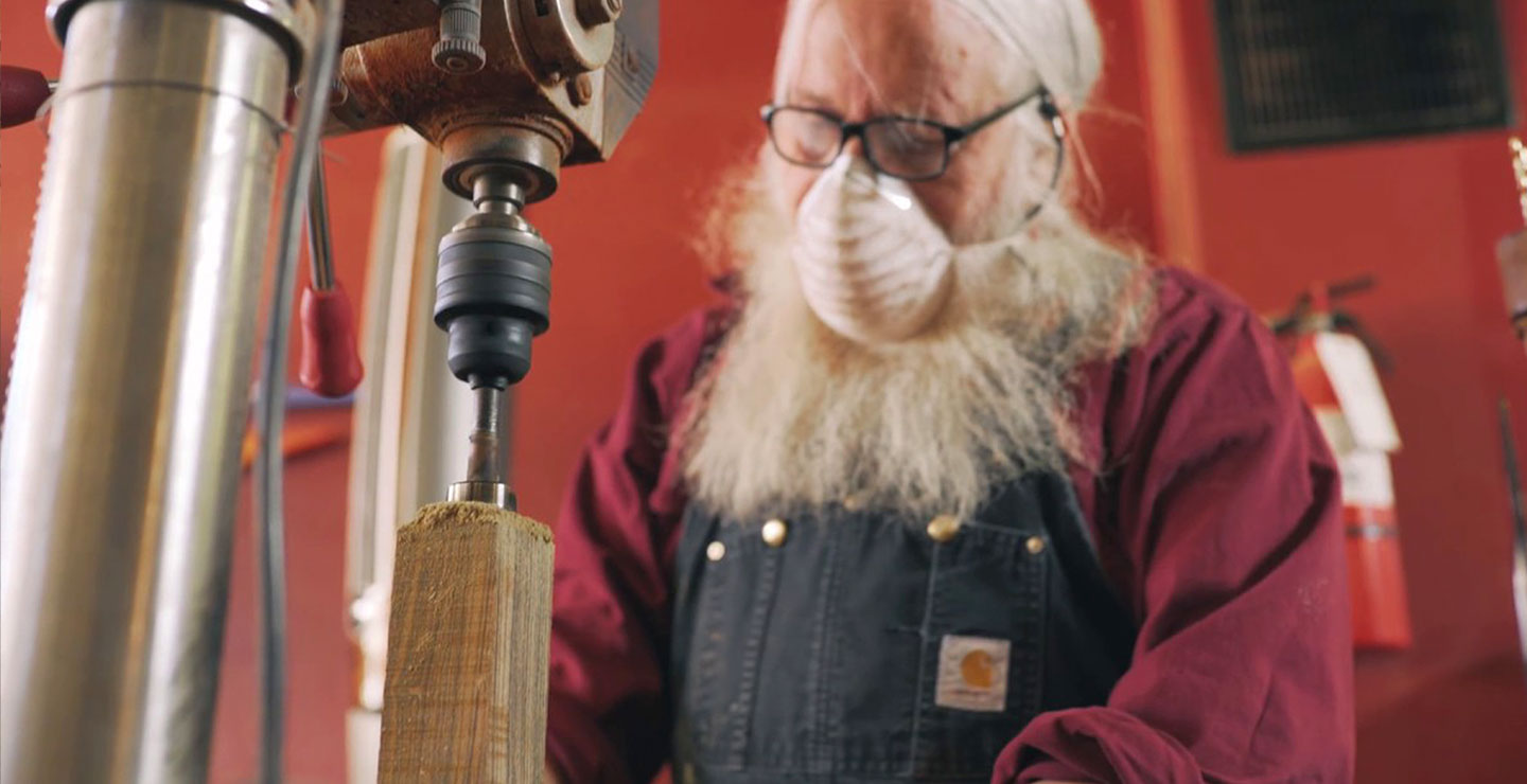 Man wearing a dust mask works with lathe