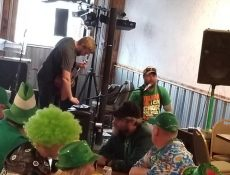 Bar customers dressed in St. Patrick's Day clothing sit around table