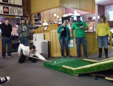 Group of people playing a pool/mini golf game