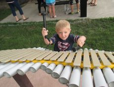 Young boy playing outdoor xylophone