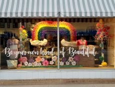 Colorful window display with trees, flowers, clothing, and a rainbow