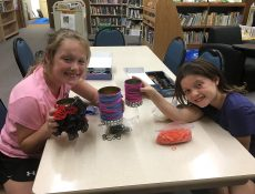 Two young girls show off their crafts