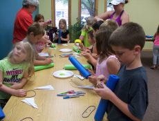 Kids working on craft with pool noodles
