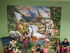 Children posing in front of a jungle mural