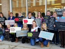 Group of women posing with signs they've made