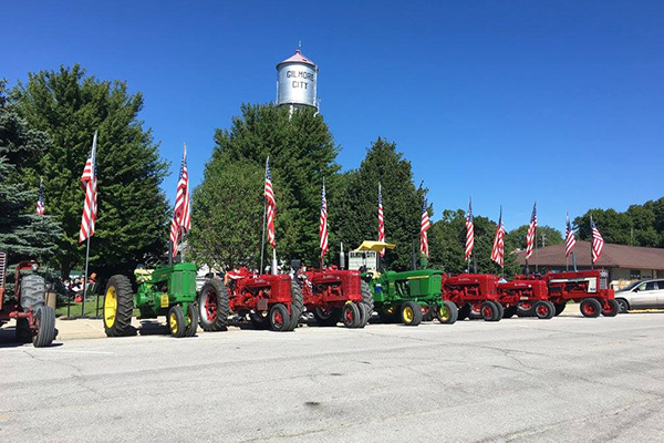 Parked red and green tractors with American flags