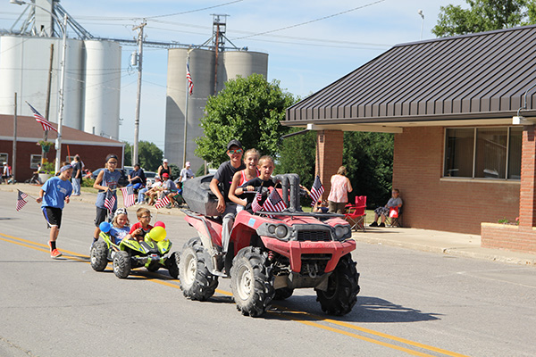 Kids riding 4-wheelers in a parade