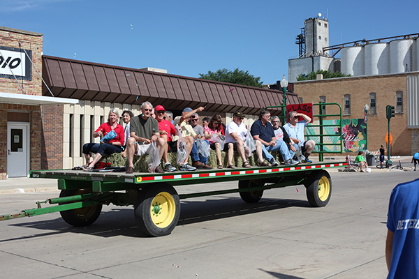 People riding on a tractor trailer during a parade