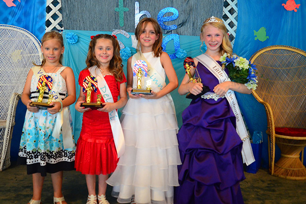 Four young girls in dresses pose with their pageant awards