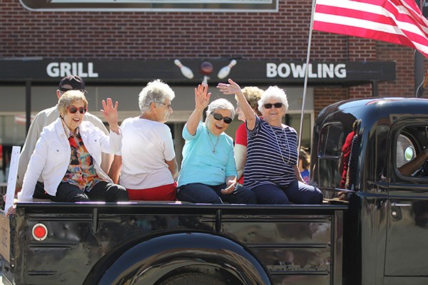 Women waving while riding in a truck bed