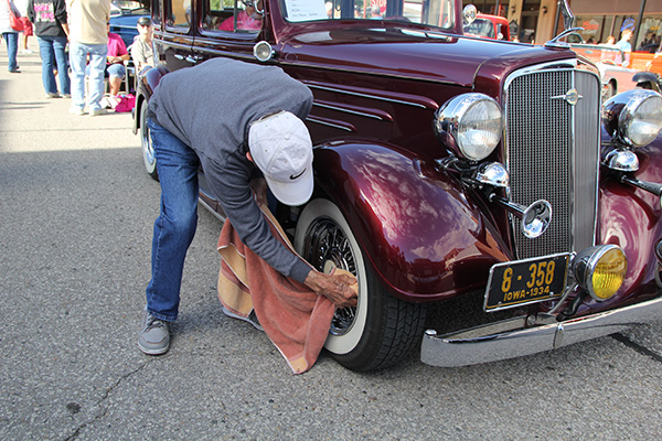 Man cleans hubcap on vintage car