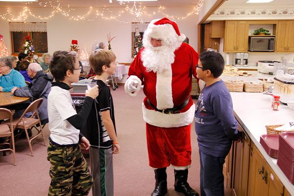Three young boys talking with Santa