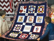 Three women holding a quilt