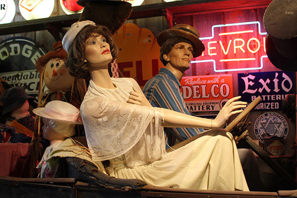 Mannequins in an old car; neon signs are lit behind them