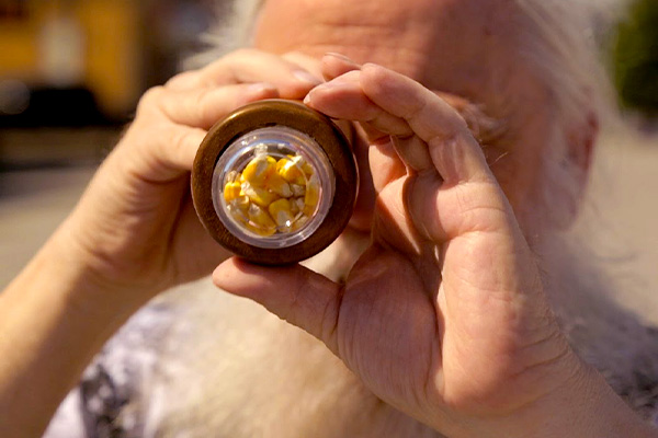Man looking through kaleidoscope with yellow corn kernels