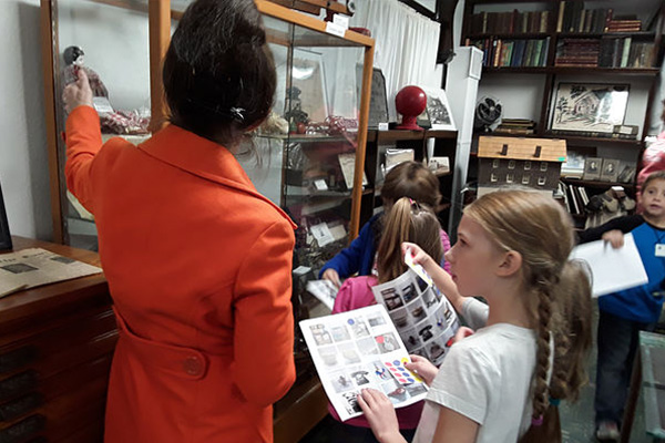 Tour guide explaining items in a display case to group of children