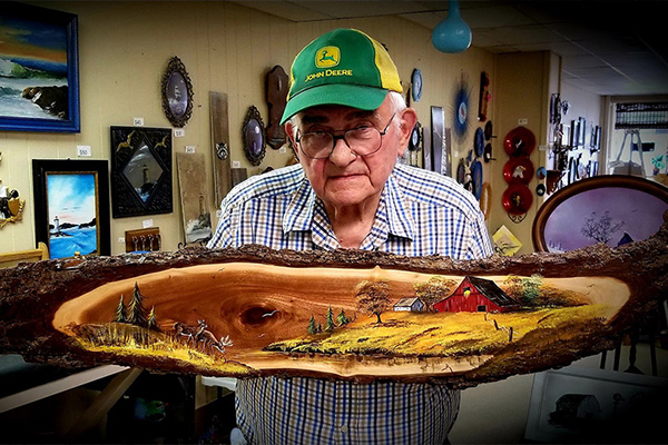 Man holds wooden slab with oil painting