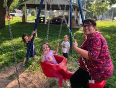 Mom and children smile while swinging